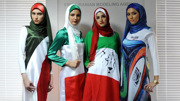 Iranian models present outfits bearing the national flag's colors and other World Cup-linked designs in Tehran on June 24, 2014