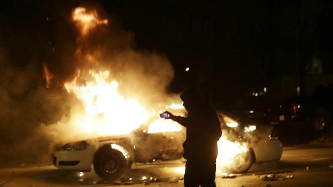 A man runs from a police car that is set on fire after a group of protesters vandalize the vehicle after the announcement of the grand jury decision Monday, Nov. 24, 2014, in Ferguson, Mo. A grand jury has decided not to indict Ferguson police officer Darren Wilson in the death of Michael Brown, the unarmed, black 18-year-old whose fatal shooting sparked sometimes violent protests. (AP Photo/Charlie Riedel)
