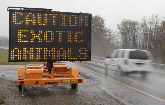 A sign warning motorists that exotic animals are on the loose rests on I-70 Wednesday, Oct. 19, 2011, near Zanesville, Ohio. Police with assault rifles stalked a mountain lion, grizzly bear and monkey