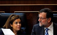 El Gobierno español no está trabajando actualmente en un nuevo plan para recortar el gasto público más allá del previsto, dijo el viernes la vicepresidenta del Ejecutivo, Soraya Sáenz de Santamaría, tras la aprobación de una batería de medidas para estimular el crecimiento económico. En la imagen, la vicepresidenta del Gobierno, Soraya Sáenz de Santamaría, (a la izquierda) muestra un documento al presidente del Gobeirno, Mariano Rajoy, en el segundo día del debate sobre el estado de la nación en el Congreso de los Diputados, en madrid, el 21 de febrero de 2013. REUTERS/Susana Vera