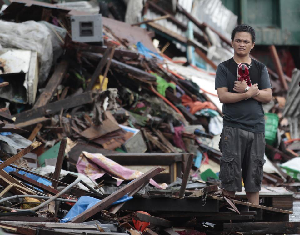 A resident looks at houses damaged by typhoon Haiyan, in Tacloban city, Leyte province central Philippines on Sunday, Nov. 10, 2013. Haiyan, one of the most powerful typhoons ever recorded slammed into central Philippine provinces Friday leaving a wide swath of destruction and scores of people dead. (AP Photo/Aaron Favila)