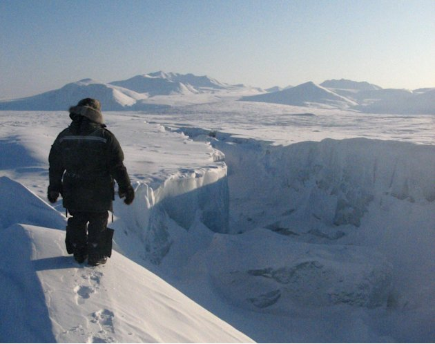 FILE - In this April 1, 2008 file photo, Canadian Ranger Samson Ejanqiaq looks along the length of one of the gaping new cracks in the Ward Hunt Ice Shelf, the largest ice shelf left in the Arctic, du