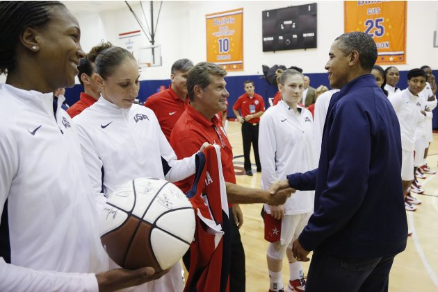 U.S. President Obama greets Catchings, Taurasi and coach Auriemma of the U.S. Olympic women's basketball team after their exhibition game against Brazil in Washington