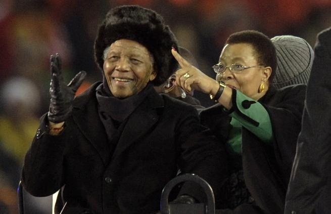 FILE -- In this file photo taken July 11, 2010 former South African President Nelson Mandela, left, with his wife Graca Machel, right, attends the final of the FIFA World Cup Soccer Tournament in Johannesburg, Mandela's last public appearance. Mandela, now old and frail, lives in seclusion in his Johannesburg home. Beyond the high walls of the house, the fighting over his image and what he stood for has already begun (AP Photo/Martin Meissner-File)