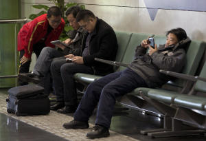 Men browse their tablet computers and smartphone at …