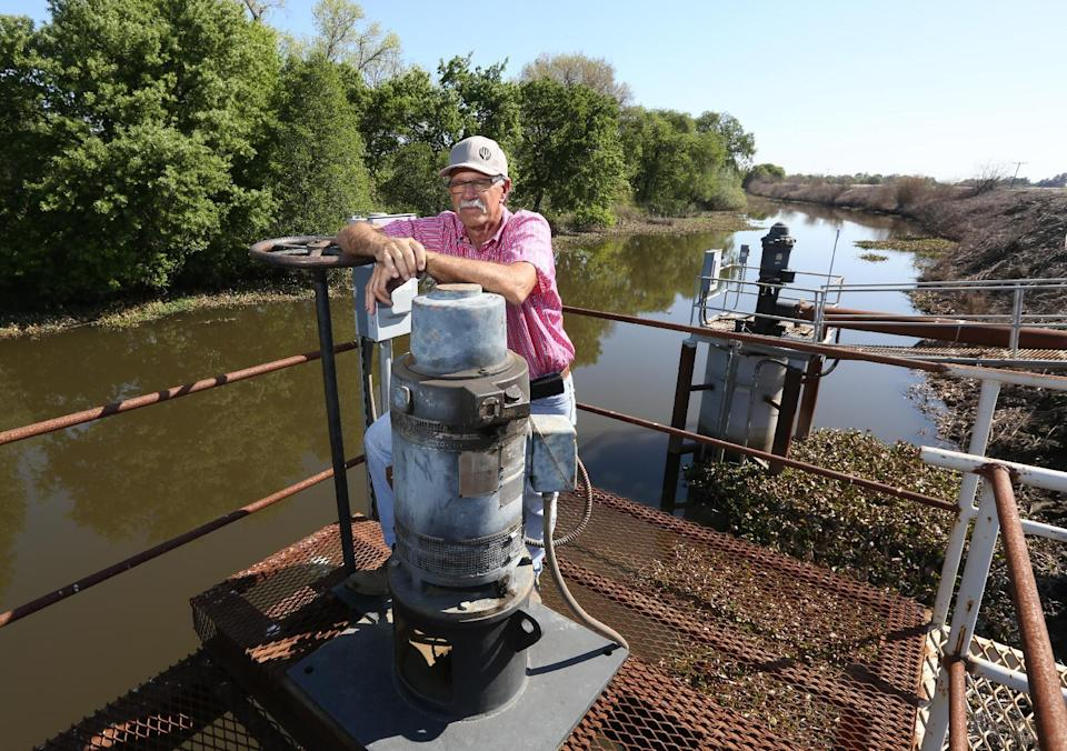 In this photo taken Friday March 27, 2015, farmer Rudy Mussi poses at one of his pumps that draws water from a slough to irrigate his farm land in the...