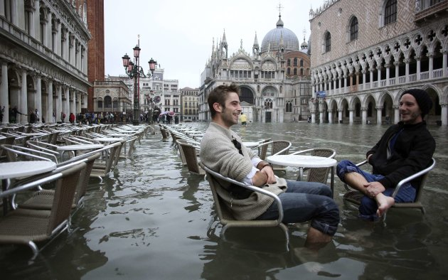Tourists sit in St. Mark Square during a period of seasonal high water in Venice