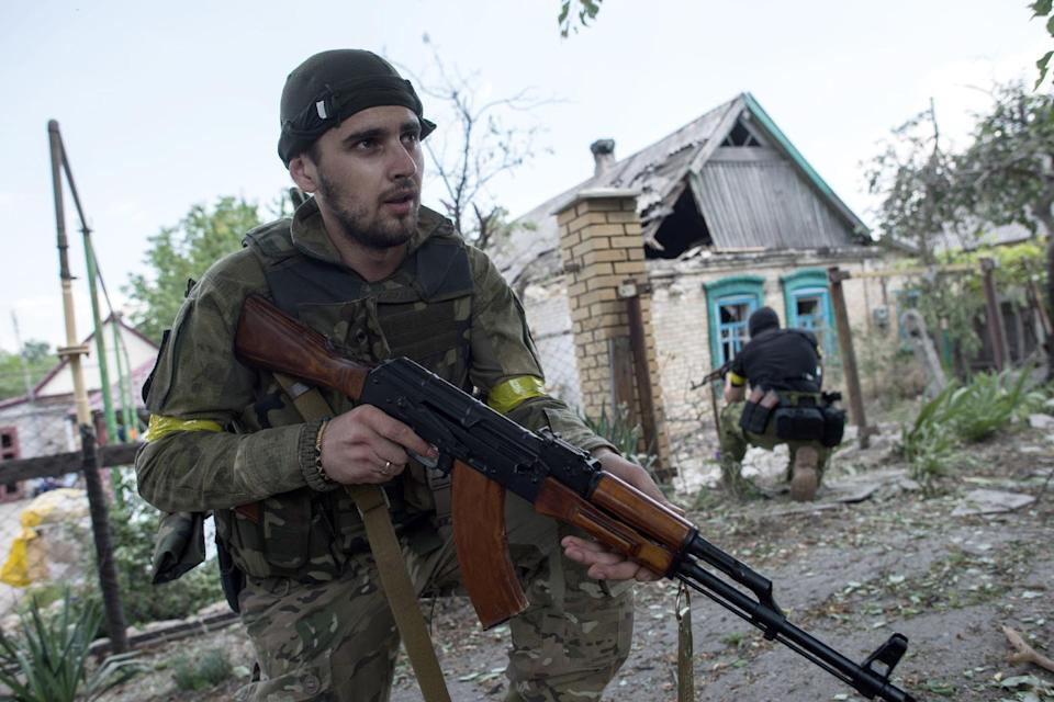 "FILE - In this June 4, 2015 file photo, Ukrainian servicemen from battalion ""Kiev1"" guard their position near a damaged house in Marinka..."