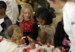 First lady Michelle Obama decorates a lollipop during a holiday decoration preview at the White House in Washington, Wednesday, Nov. 28, 2012. Obama joined school children as they decorated holiday ...