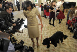 First lady Michelle Obama, accompanied by first dog Bo, walks past reporters during a visit to the State Dining Room of the White House in Washington, Wednesday, Nov. 28, 2012, during a preview of ...