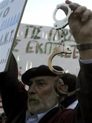 A protester holds handcuffs during an anti-government  demonstration staged by civil servants outside the Greek Parliament in  Athens, Tuesday, April 27, 2010. Greece's debt crisis intensified  Tuesday as its credit rating cut to junk status. (AP Photo/Marita  Pappa)