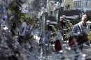 Residents of Leblon neighborhood are reflected in broken glass in Rio de Janeiro