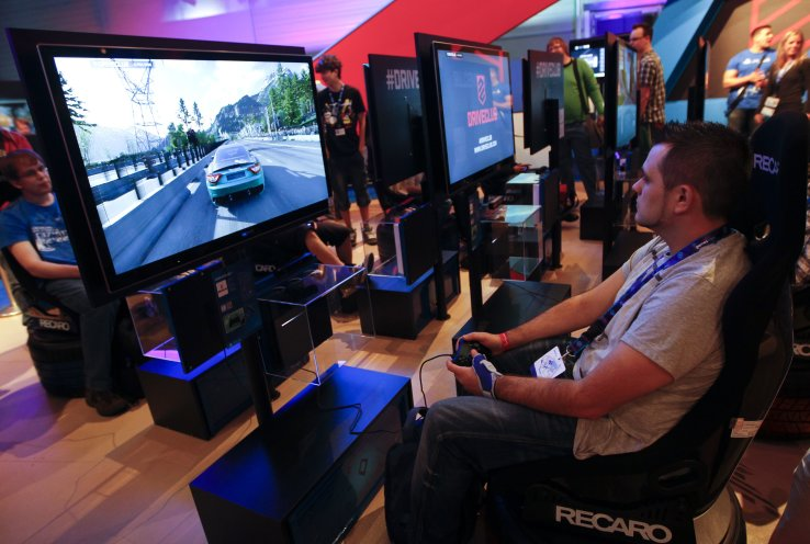 """Visitors play """"Driveclub"""" with a Playstation 4 at the Sony exhibition stand during the Gamescom 2013 video games fair in Cologne"""