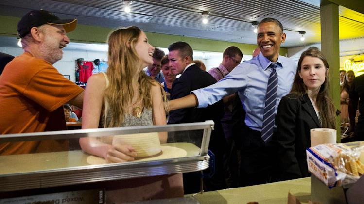 President Barack Obama jokes with patrons as he orders barbecue for himself and the people in the front of the line at Franklin Barbecue in Austin, Texas, Thursday, July 10, 2014. Austin is the final leg in his three city trip before returning to Washington. At right is Kinsey Button, who introduced the President in his speech earlier that afternoon. (AP Photo/Jacquelyn Martin)