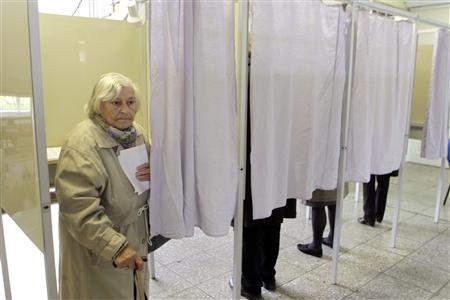 A woman leaves a ballot booth after casting her vote during general elections in Vilnius October 14, 2012. REUTERS/Ints Kalnins