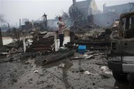 A resident looks over the remains of burned homes in the Rockaways section of New York, October 30, 2012. REUTERS/Keith Bedford