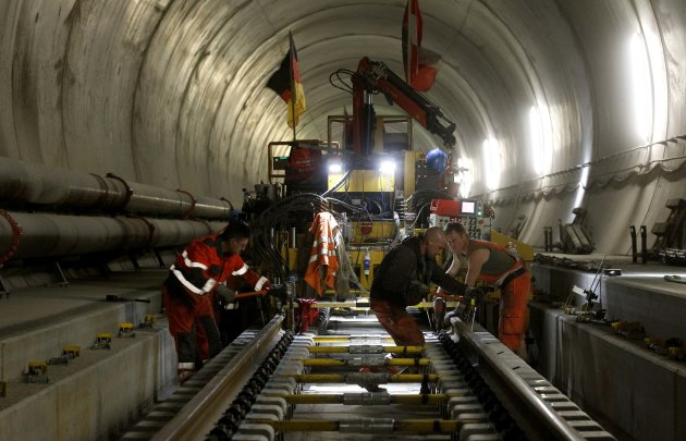 Workers use torque wrenches to fix screw nuts during the installation of the railway tracks in the NEAT Gotthard Base tunnel near Erstfeld