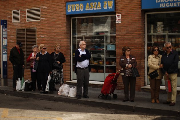 People wait at a bus stop in front of an Asian shop after shopping in Malaga