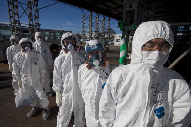 FILE - In this Saturday, Nov. 12, 2011 file photo, workers in protective suits and masks wait to enter the emergency operation center at the crippled Fukushima Dai-ichi nuclear power station in Okuma, Japan. Tokyo Electric Power Co., the utility that runs the Fukushima Dai-ichi plant that melted down in March 2011 after being hit by a tsunami, is finding that it can barely meet the headcount of workers required to keep the three broken reactors cool while fighting power outages and leaks of tons of radiated water, said current and former nuclear plant workers and others familiar with the situation at Fukushima. (AP Photo/David Guttenfelder, Pool)