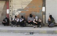 Free Syrian Army members, with covered faces and holding weapons, sit by the side of a street in Qaboun district, Damascus June 11, 2012. REUTERS/Stringer