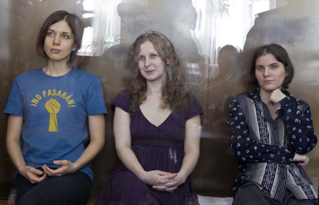 """FILE - In this Wednesday, Aug. 8, 2012 file photo feminist punk group Pussy Riot members, from left, Nadezhda Tolokonnikova, Maria Alekhina and Yekaterina Samutsevich sit in a glass cage at a court room in Moscow, Russia. The Russian Orthodox Church on Sunday Sept. 30, 2012, asked for clemency for three jailed members of the rock band Pussy Riot if they repent for their """"punk prayer"""" for deliverance from President Vladimir Putin at Moscow's main cathedral, a statement that came a day before an appeal hearing and appeared to reflect a desire to put an end to the case that has caused an international outrage. (AP Photo/Misha Japaridze, file)"""