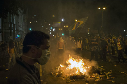 Protesters, one holding a Brazilian flag,  burn trash to block a street near the sate legislative assembly building during a protest in Rio de Janeiro, Brazil, Monday, June 17, 2013.  in Rio de Janeiro, Brazil, Monday, June 17, 2013.  Officers in Rio fired tear gas and rubber bullets when a group of protesters invaded the state legislative assembly and threw rocks and flares at police. Protesters massed in at least seven Brazilian cities Monday for another round of demonstrations voicing disgruntlement about life in the country, raising questions about security during big events like the current Confederations Cup and a papal visit next month.  (AP Photo/Felipe Dana)