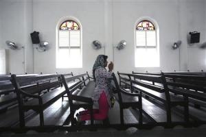 A woman prays inside the church of Our Lady of Lourdes …