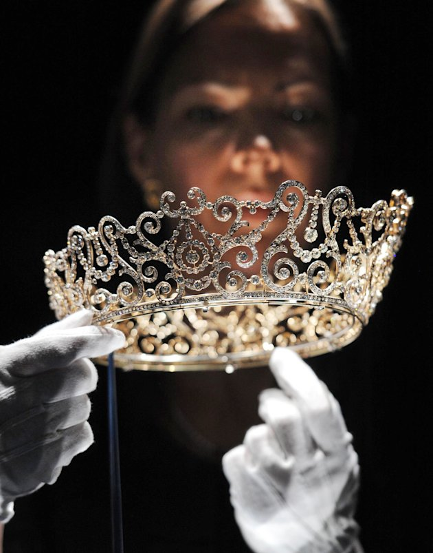 This Thursday June 28, 2012 photo shows curator Caroline de Guitaut, holding the Delhi Durbar Tiara, on show for the first time and made to mark the succession of King George V as King Emperor in 1911