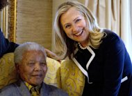 FILE - In this Aug. 6, 2012 file photo, U.S. Secretary of State Hillary Rodham Clinton, right, meets with former South Africa President Nelson Mandela, 94, at his home in Qunu, South Africa. There may be no living figure so revered as Mandela around the world as a symbol of sacrifice and reconciliation, his legacy forged in the fight against apartheid, the system of white minority rule that imprisoned him for 27 years. (AP Photo/Jacquelyn Martin, Pool-File)