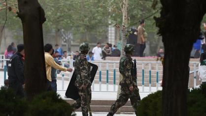 Paramilitary police patrol beside the central square in Hotan, in China's western Xinjiang region