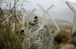 Macedonian soldiers erect a metal fence on the border …