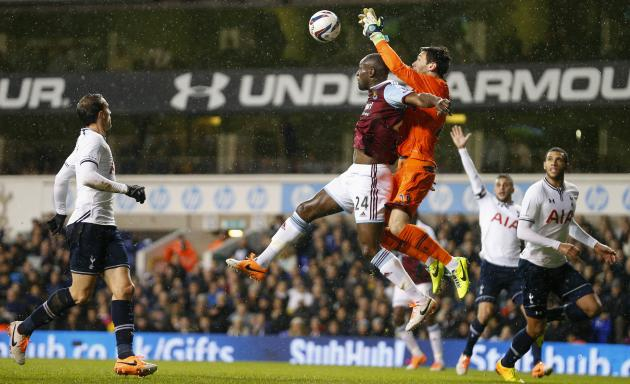 Lloris of Tottenham Hotspur beats Cole of West Ham United to the ball during their English League Cup soccer match at White Hart Lane, London