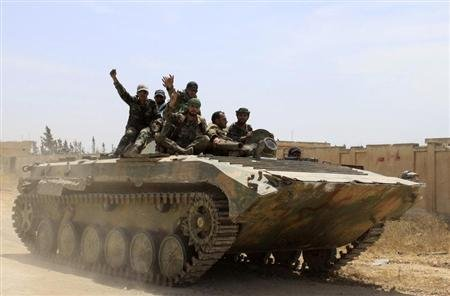 Soldiers loyal to the Syrian regime gesture while on their military vehicle in the village of Debaa near Qusair, after the Syrian army took control of the village from rebel fighters June 7, 2013. REUTERS/Rami Bleible