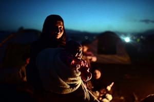 A woman holds her crying baby at a makeshift camp by …