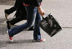 A shopper walks down Fifth Avenue with an Abercrombie …