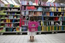 A young girl looks at school at school stationery in a supermarket in Nice