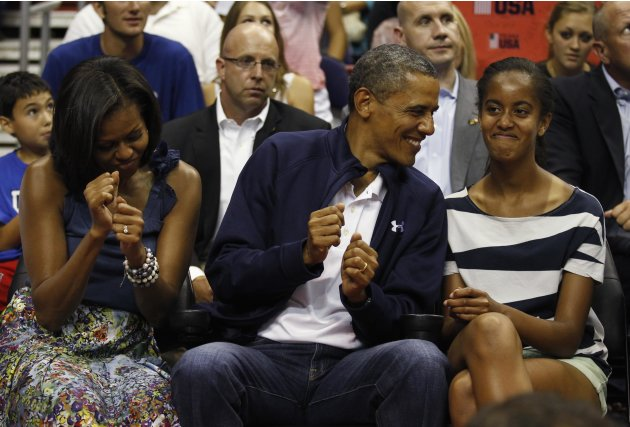 U.S. President Obama and first lady Michelle Obama move to the music as daughter Malia looks on as they attend the Olympic men's exhibition basketball game between Team USA and Brazil in Washingto