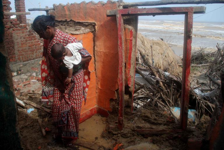 A villager carried her child as she stands over the remains of her beachside home at Padampeta Village, about 200 kilometers south from the eastern Indian city of Bhubaneswar, on October 13, 2013