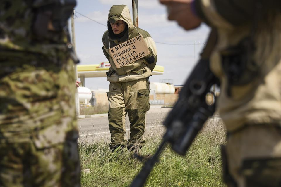 "A man stands tied to a post by pro-Russian rebels, accused of stealing from local people, with a poster around his neck reading  ""I am marauder, ..."