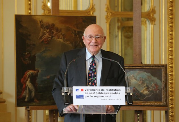 American Thomas Selldorff, speaks during a ceremony at the Culture Ministry in Paris, France, Tuesday, March 19, 2013, to return seven paintings taken from their Jewish owners during World War II, as part of ongoing efforts to give back hundreds of looted artworks that still hang in the Louvre and other French museums. Selldorff reclaimed six German and Italian paintings that his grandfather, Richard Neumann, was forced to sell during World War II to flee Nazi occupation, and one other painting was returned to other recipients. In the background painting left, Sebastiano Ricci, (Belluno, 1659 - Venice, 1734), Abraham and the three angels, painting right, Gaspare Diziani(Belluno, 1689 - Venice, 1767), Allegory of Venice. Sign in front reads: ceremony of return of seven paintings spoils from the Nazi regime. (AP Photo/Michel Euler)