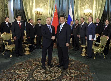 Russia's President Vladimir Putin shakes hands with China's President Xi Jinping during their meeting at the Kremlin in Moscow