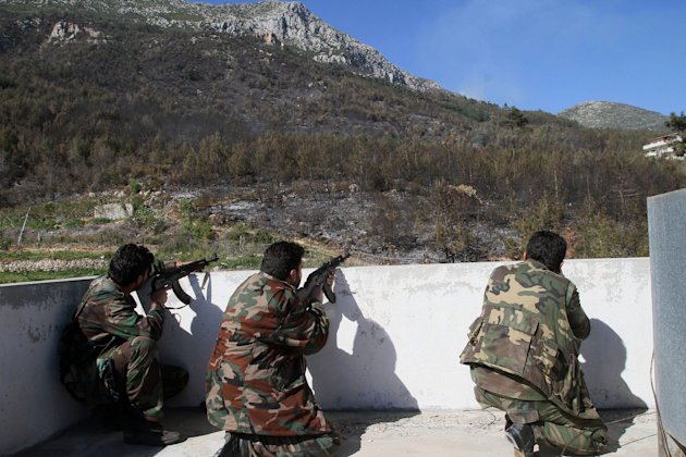 In this photo taken Thursday, March 27, 2014, Syrian government soldiers take position during clashes with rebels in Misherfeh town in the province of Latakia, Syria. Syrian forces on Thursday bombarded rebel positions with artillery and warplanes in the Mediterranean coastal province of Latakia, trying to push back opposition fighters who over the past week made rare territorial gains in President Bashar Assad's ancestral heartland. (AP Photo)