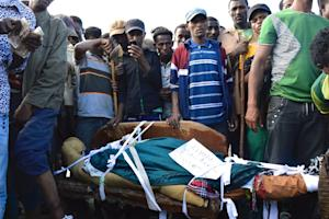 Ethiopians stand near the body of an Oromo protester …