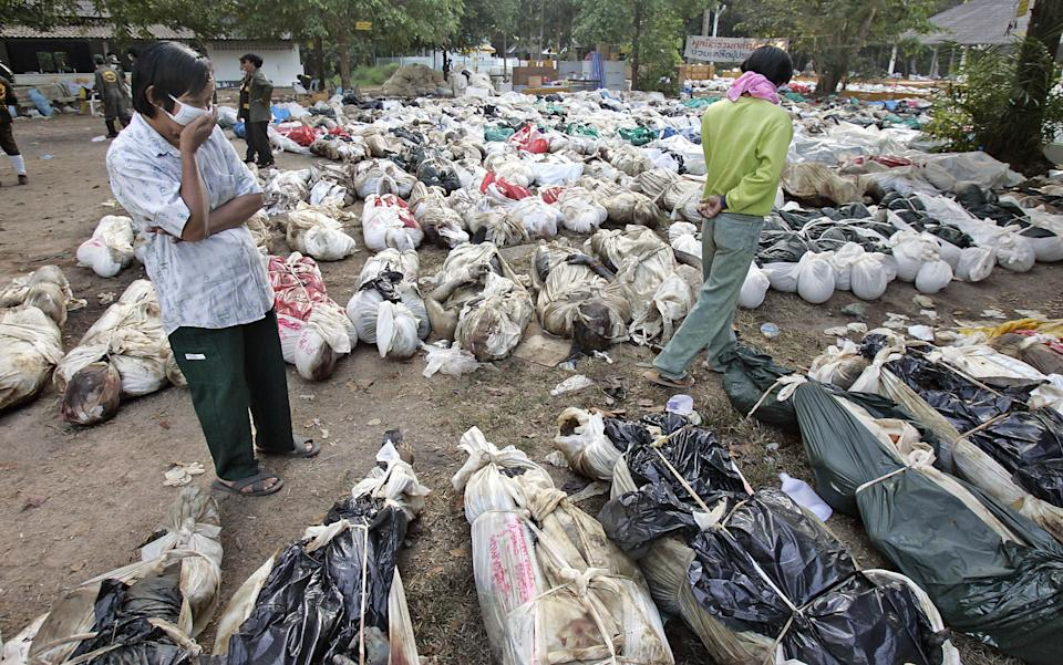 FILE - In this Dec. 30, 2004 file photo, Thais walk outside a Buddhist temple, near Takuapa, Thailand, where more than 1,000 bodies have been gathered...