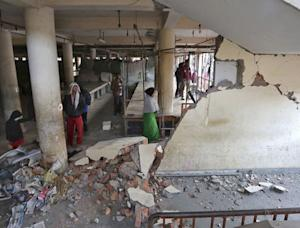 People look at a damaged building at a market place …