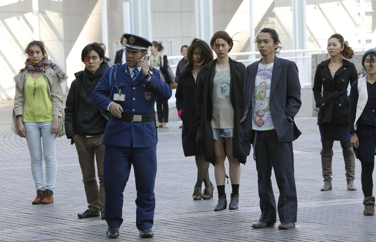 A guard speaks on a mobile phone in front of demonstrators participating in a silence protest in front of a conference hall where the Intergovernmental Panel on Climate Change is meeting in Yokohama, near Tokyo, Monday, March 31, 2014. (AP Photo/Shizuo Kambayashi)