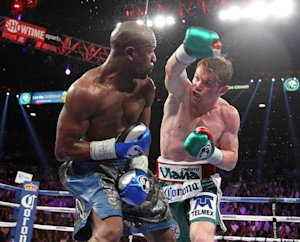 Saul Alvarez (R) throws a right at Floyd Mayweather …