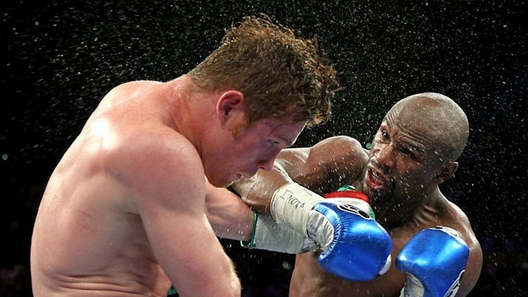 Floyd Mayweather (R) throws a right at Saul Alvarez during their WBC/WBA super welterweight fight on September 14, 2013