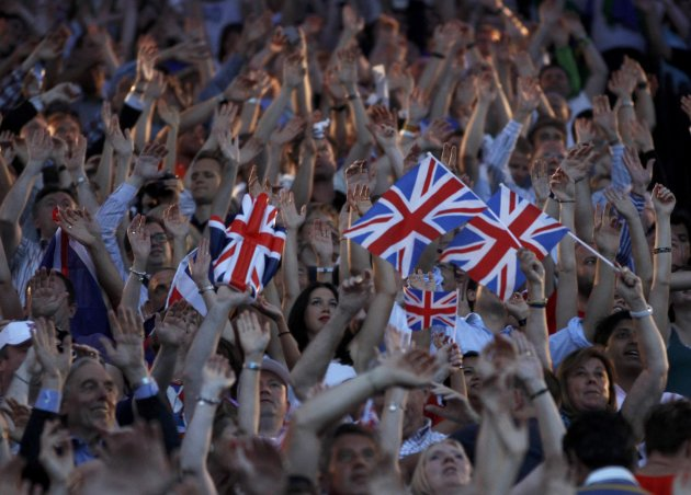 Guests stand and wave Britain's flag during the closing ceremony of the London 2012 Olympic Games