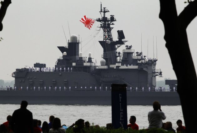 People watch as the Japanese Navy ship, JS Shirane, makes its way through the New York Harbor